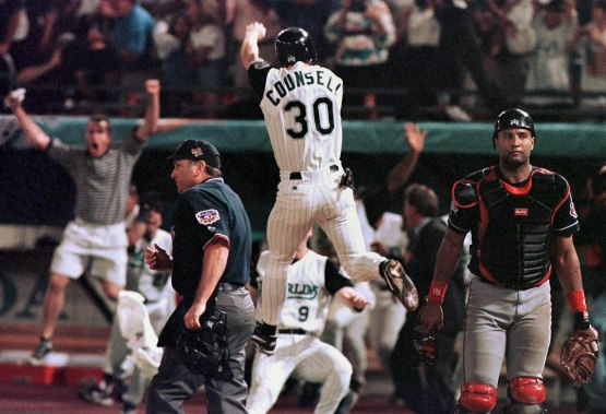 MIAMI, : Florida Marlins player Craig Counsell jumps in the air after crossing the plate with the winning run as Cleveland Indians catcher Sandy Alomar (R) walks off the field at the end of game seven of the World Series 26 October at Pro Player Stadium. The Marlins won in 11 innings 3-2. AFP PHOTO/Jeff HAYNES (Photo credit should read JEFF HAYNES/AFP/Getty Images)
